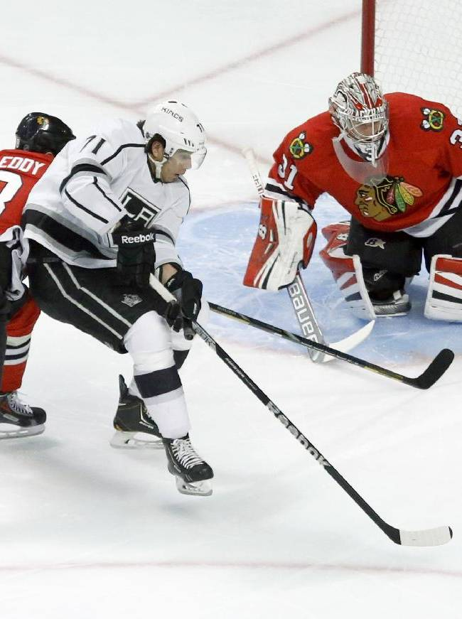 Chicago Blackhawks defenseman Nick Leddy (8) keeps Los Angeles Kings center Jordan Nolan from getting his own rebound as goalie Antti Raanta defends during the first period of an NHL hockey game Monday, Dec. 30, 2013, in Chicago