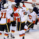 Calgary Flames' Mason Raymond (21), Mikael Backlund (11), TJ Brodie (7) and Johnny Gaudreau (13) celebrate after Brodie scored during the third period of an NHL hockey game against the Winnipeg Jets in Winnipeg, Manitoba, Sunday, Oct. 19, 2014 The Associa