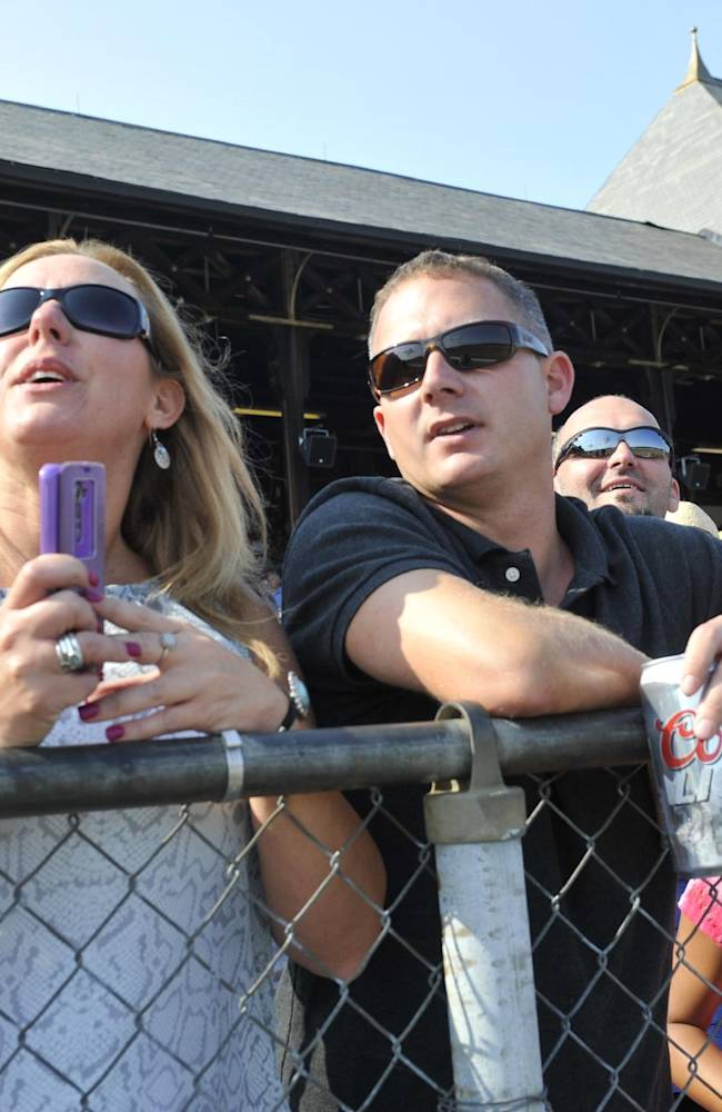 Michele Robinson ,left, and Tim Lussier of Saratoga Springs, N.Y., watch racing action on opening day of the horse racing season at Saratoga Race Course in Saratoga Springs, N.Y., Friday, July 18, 2014