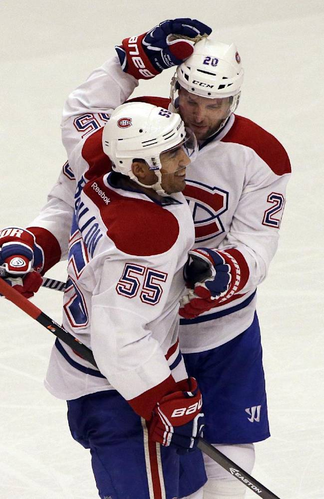 Montreal Canadiens' Francis Bouillon (55) celebrates with Thomas Vanek (20) after scoring his goal during the third period of an NHL hockey game against the Chicago Blackhawks in Chicago, Wednesday, April 9, 2014. The Blackhawks won 3-2 in overtime