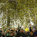 Members of the Emerald City Supporters sing and chant as they take part in the traditional March to the Match under holiday lights before an MLS western conference semifinal soccer match between the Seattle Sounders and FC Dallas, Monday, Nov. 10, 2014, i