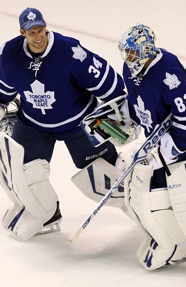 Maple Leafs' goalie James Reimer congratulates Christopher Gibson after an NHL pre-season game, Sunday Sept. 15, 2013 in London, Ontario