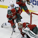 Minnesota Wild goalie Darcy Kuemper (35) covers the puck as Wild defenseman Mathew Dumba (55) and San Jose Sharks center Joe Pavelski (8) chase it during the first period of an NHL hockey game in St. Paul, Minn., Thursday, Oct. 30, 2014. The Wild won 4-3