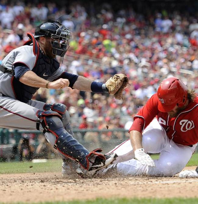 In this June 9, 2013, file photo, Washington Nationals' Jayson Werth, right, is out at the plate as Minnesota Twins catcher Ryan Doumit hangs on to the ball during a baseball game in Washington. The Atlanta Braves acquired Doumit from the Twins on Wednesday, Dec. 18, 2013, for left-hander Sean Gilmartin