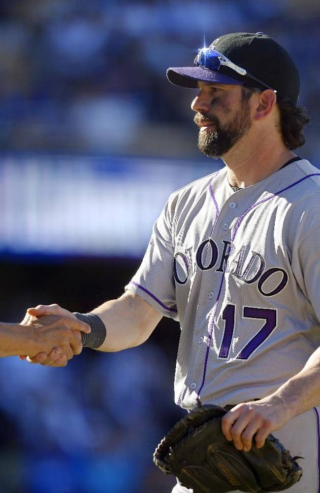 Colorado Rockies manager Walt Weiss, left, shakes hands with Todd Helton after the Rockies defeated the Los Angeles Dodgers 2-1 in a baseball game, Sunday, Sept. 29, 2013, in Los Angeles. Helton was playing in the final game of his career