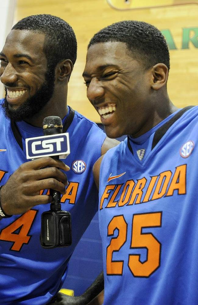Florida's Patric Young (4) and DeVon Walker (25) kid around with a microphone during the NCAA college basketball team's media day in Gainesville, Fla., Wednesday, Oct. 9, 2013