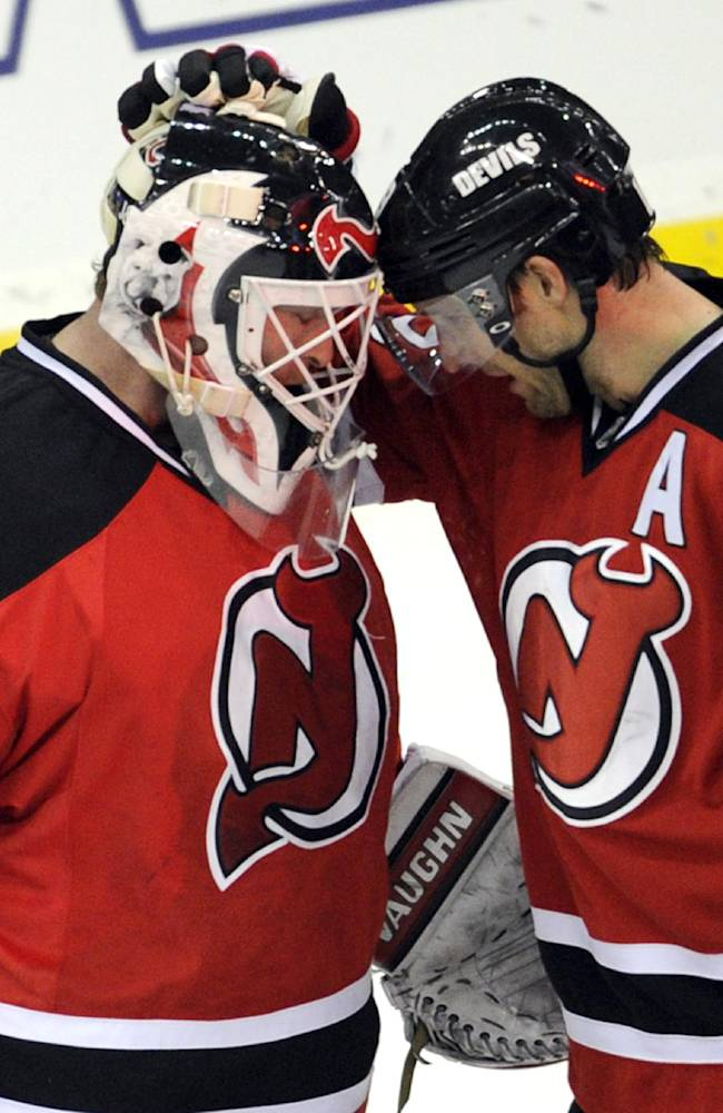 New Jersey Devils goaltender Martin Brodeur, left, celebrates with Travis Zajac after the Devils defeated the Tampa Bay Lightning 2-1 in an NHL hockey game Tuesday, Oct. 29, 2013, in Newark, N.J