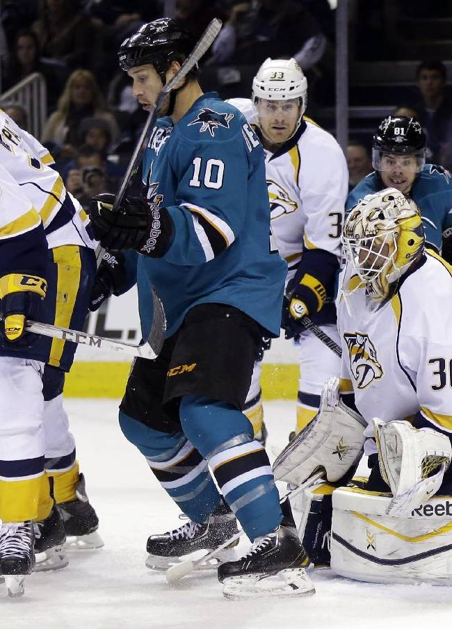 Nashville Predators defenseman Roman Josi (59), of Sweden, deflects a shot in front of San Jose Sharks center Andrew Desjardins (10) and Predators goalie Carter Hutton (30) during the first period of an NHL hockey game Saturday, April 5, 2014, in San Jose, Calif
