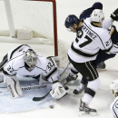 Los Angeles Kings goalie Jonathan Quick, left, grabs a loose puck as St. Louis Blues' Jori Lehtera, of Finland, is pushed out of the way by Kings' Alec Martinez (27) during the first period of an NHL hockey game Tuesday, Dec. 16, 2014, in St. Louis The As