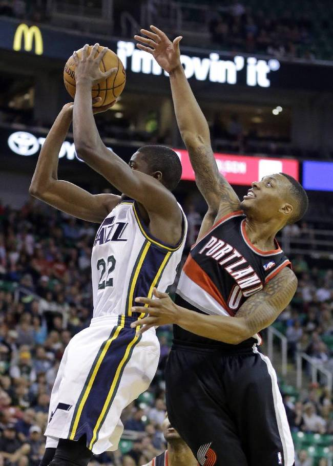 Portland Trail Blazers' Damian Lillard (0) defends against Utah Jazz's Justin Holiday (22) in the second half during an NBA preseason basketball game Wednesday, Oct. 16, 2013, in Salt Lake City. The Trail Blazers won 99-92