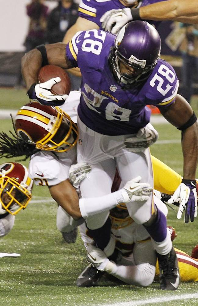 Minnesota Vikings running back Adrian Peterson (28) tries to break a tackle by Washington Redskins strong safety Brandon Meriweather during the first half of an NFL football game Thursday, Nov. 7, 2013, in Minneapolis