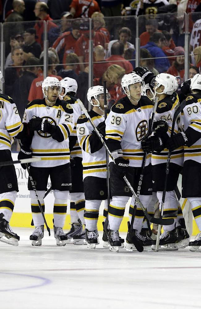 Members of the Boston Bruins celebrate beating the Washington Capitals in a shootout after a preseason NHL hockey game, Tuesday, Sept. 17, 2013, in Baltimore. Boston won 3-2