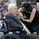 New Orleans Saints owner Tom Benson reacts as his wife Gayle Benson holds his hand at the unveiling of a statue of him outside the Mecedes-Benz Superdome in New Orleans, Tuesday, Sept. 2, 2014 The Associated Press