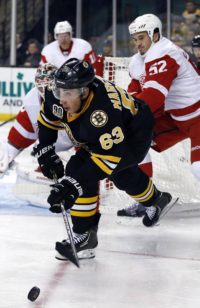 Boston Bruins left wing Brad Marchand (63) looks to pass the puck against the defense of Detroit Red Wings defenseman Jonathan Ericsson (52) in the second period of an NHL hockey game in Boston, Monday, Oct. 14, 2013
