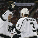 Los Angeles Kings' Drew Doughty, left, celebrates a goal by teammate Jeff Carter with Brayden McNabb (3) during the first period of an NHL hockey game against the Arizona Coyotes Saturday, Oct. 11, 2014, in Glendale, Ariz The Associated Press