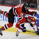 New Jersey Devils' Tuomo Ruutu, left, of Finland, checks Florida Panthers' Dmitry Kulikov, of Russia, during the third period of an NHL hockey game Monday, March 31, 2014, in Newark, N.J. The Devils won 6-3 The Associated Press