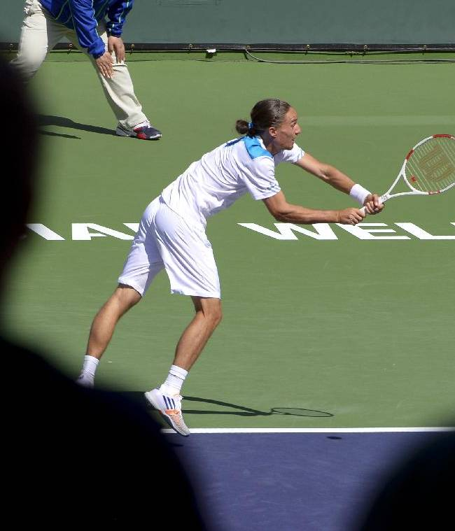 Alexandr Dolgopolov, of Ukraine, returns a shot to Roger Federer, of Switzerland, during their semifinal match at the BNP Paribas Open tennis tournament, Saturday, March 15, 2014, in Indian Wells, Calif