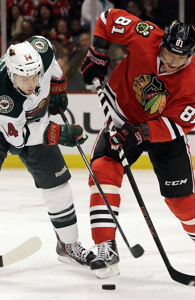 Minnesota Wild's Justin Fontaine (14) and Chicago Blackhawks' Marian Hossa (81) battle for the puck during the first period of an NHL hockey game in Chicago, Saturday, Oct. 26, 2013