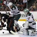 Anaheim Ducks right wing Corey Perry (10) is knocked to the ice by Minnesota Wild defenseman Jonas Brodin (25), of Sweden with goalie Josh Harding (37) defending from a rebound shot in the second period of an NHL hockey game Wednesday, Dec. 11, 2013 in An