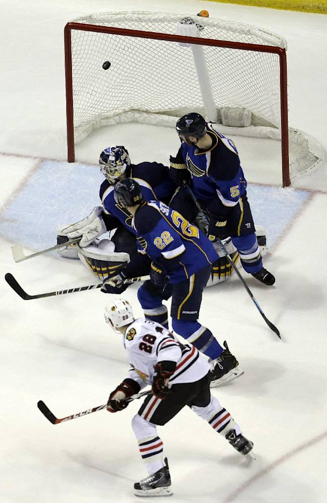 Chicago Blackhawks' Ben Smith (28) scores past St. Louis Blues goalie Ryan Miller, Kevin Shattenkirk (22) and Barret Jackman (5) during the second period in Game 5 of a first-round NHL hockey playoff series Friday, April 25, 2014, in St. Louis