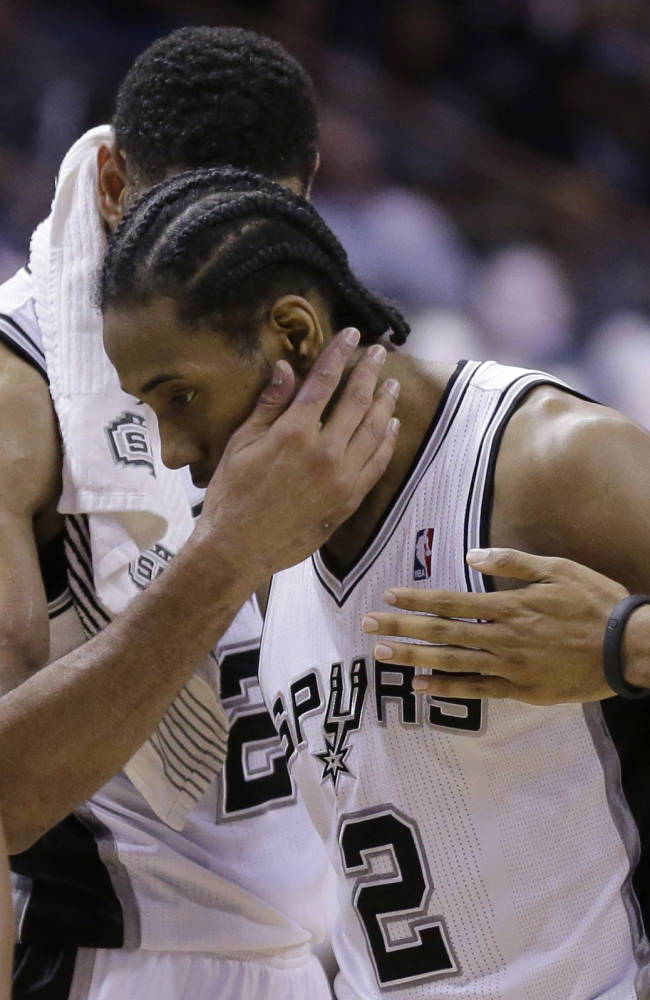 San Antonio Spurs' Kawhi Leonard (2) is hugged by teammate Tim Duncan during the second half of Game 5 of a Western Conference semifinal NBA basketball playoff series, Wednesday, May 14, 2014, in San Antonio. San Antonio won 104-82