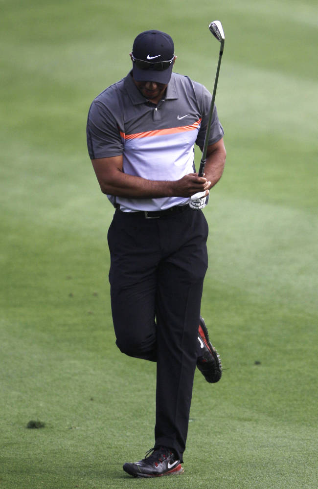 Tiger Woods from the U.S. reacts on the 14th hole during the first round of the Dubai Desert Classic golf tournament in Dubai, United Arab Emirates, Thursday Jan. 30, 2014