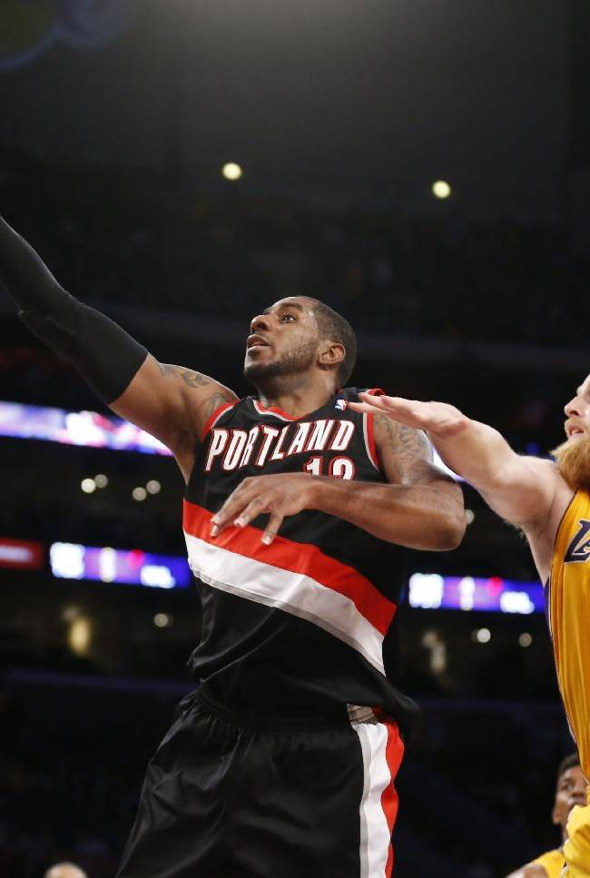 Portland Trail Blazers forward LaMarcus Aldridge, left, goes to the hoop in front of Los Angeles Lakers center Chris Kaman, right, during the second half of an NBA basketball game in Los Angeles, Tuesday, April 1, 2014. The Trail Blazers won 124-112
