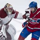Phoenix Coyotes goalie Mike Smith fends off Montreal Canadiens' David Desharnais during the third period of an NHL hockey game Tuesday, Dec. 17, 2013, in Montreal. (AP Photo/The Canadian Press, Paul Chiasson)