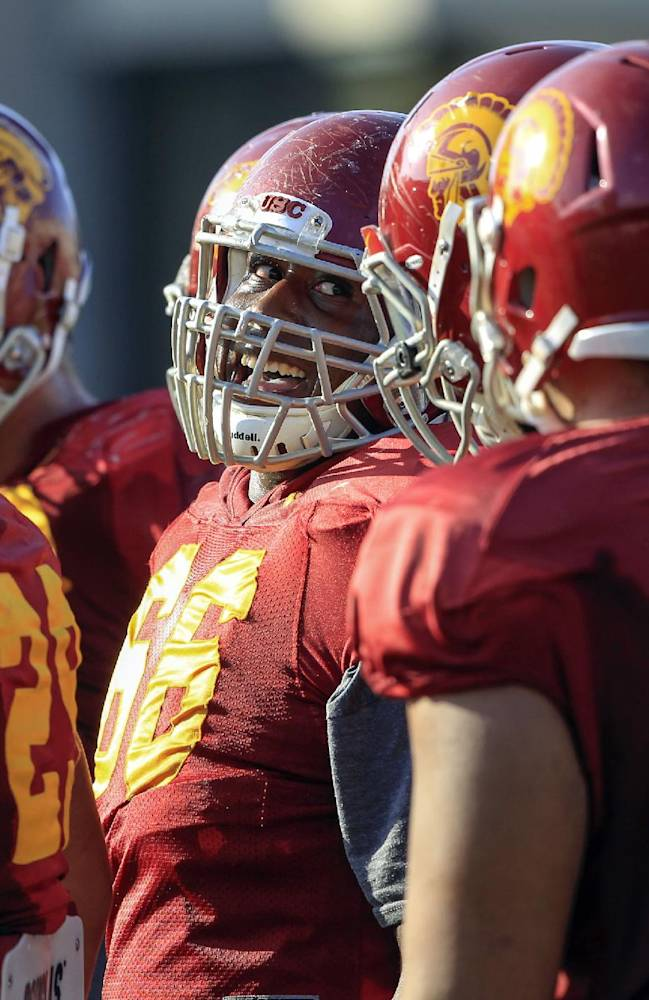 Southern California center offensive guard Marcus Martin, center, smiles during open NCAA college football practice at their Los Angeles campus on Wednesday, Oct. 2, 2013