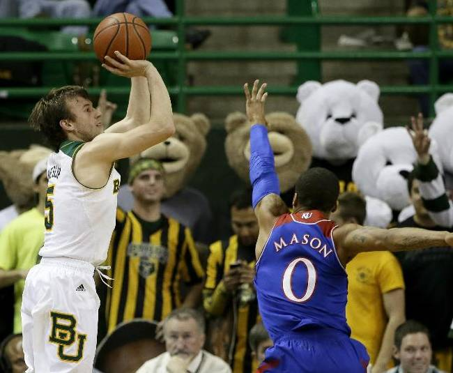 Baylor guard Brady Heslip (5) goes up for a 3-point basket as Kansas' Frrank Mason (0) defends in the first half of an NCAA college basketball game, Tuesday, Feb. 4, 2014, in Waco, Texas
