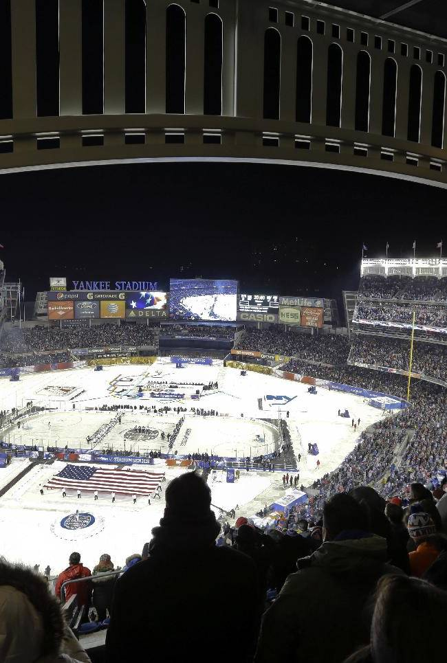Fans stand during the national anthem before an outdoor NHL hockey game between the New York Islanders and the New York Rangers Wednesday, Jan. 29, 2014, at Yankee Stadium in New York