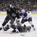 Los Angeles Kings' Trevor Lewis, bottom, falls to the ice as he and teammate Dustin Penner, left, fight for the puck with St.