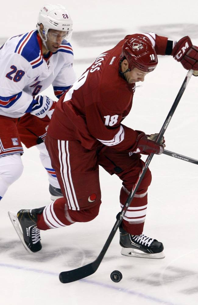 Dominic Moore (28) of the Rangers defends against David Moss of the Coyotes  during the first period of an NHL hockey game Thursday, Oct. 3, 2013, in Glendale, Az