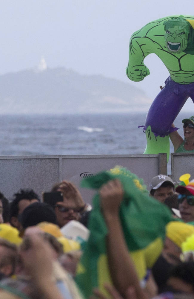 A woman holds up an inflatable Hulk doll, a reference to Brazil's soccer player Hulk, at the FIFA Fan fest area where fans gather to watch the World Cup soccer game between Brazil and Croatia on Copacabana beach in Rio de Janeiro, Brazil, Thursday, June 12, 2014. (AP Photo/Silvia Izquierdo)