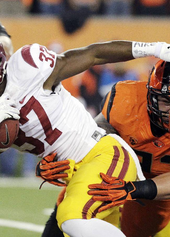 Southern California running back Javorius Allen, left, eludes the grasp of Oregon State defender Mana Rosa on his way to scoring a touchdown during the first half of an NCAA college football game in Corvallis, Ore., Friday, Nov. 1, 2013