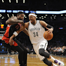 Brooklyn Nets' Paul Pierce (34) drives the ball around Toronto Raptors' Amir Johnson (15) in the first half of an NBA basketball game on Monday, March 10, 2014 at Barclays Center in New York The Associated Press