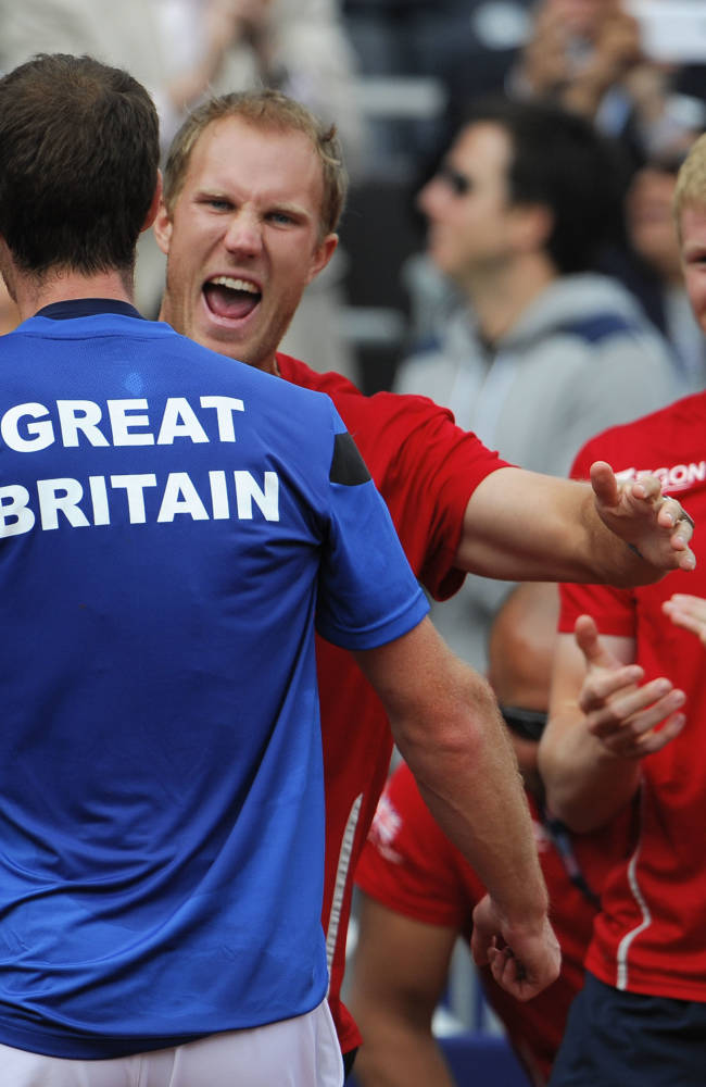 Britain's Andy Murray, left, is hugged by teammate Dominic Inglot, center, as Kyle Edmund, right, looks on after Murray defeated United States' Sam Querrey at the Davis Cup tennis matches on Sunday, Feb. 2, 2014, in San Diego