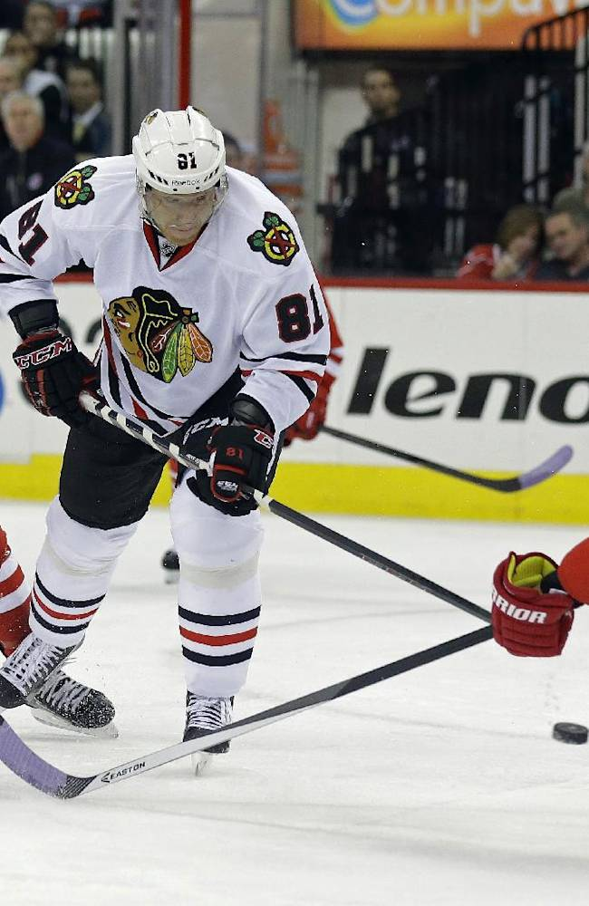 Chicago Blackhawks' Marian Hossa (81), of Slovakia, shoots past Carolina Hurricanes' Ron Hainsey (65) as Hurricanes' Riley Nash defends during the first period of an NHL hockey game in Raleigh, N.C., Tuesday, Oct. 15, 2013