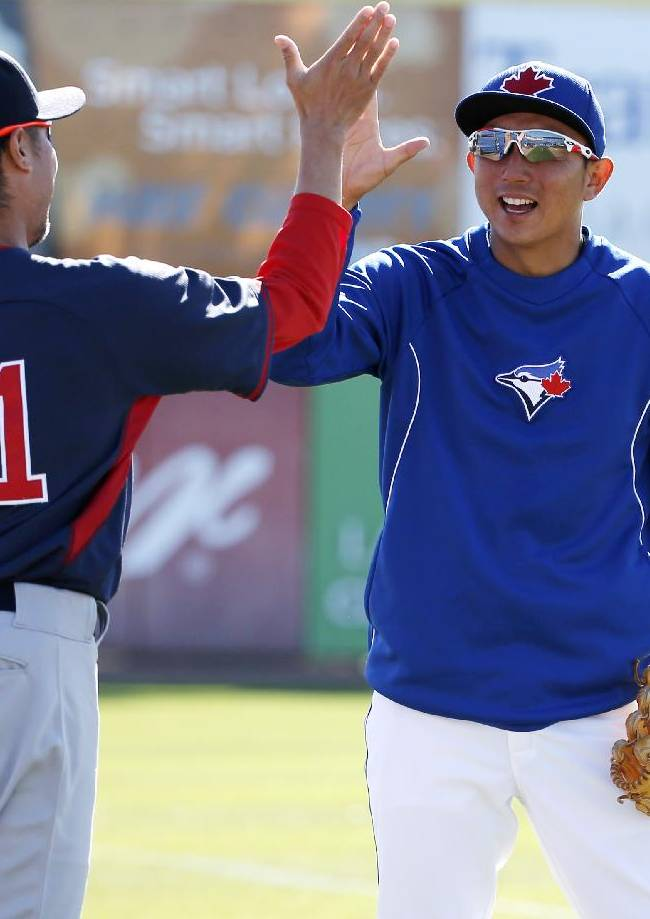 Boston Red Sox pitcher Shunsuke Watanabe, left, and Toronto Blue Jays third baseman Munenori Kawasaki greet each other before a spring exhibition baseball game in Dunedin, Fla., Friday, March 14, 2014