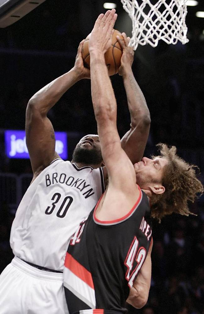 Portland Trail Blazers center Robin Lopez (42) tries to block Brooklyn Nets power forward Reggie Evans (30) as Evans goes up for a layup in the first half of their their NBA basketball game at the Barclays Center, Monday, Nov. 18, 2013, in Brooklyn