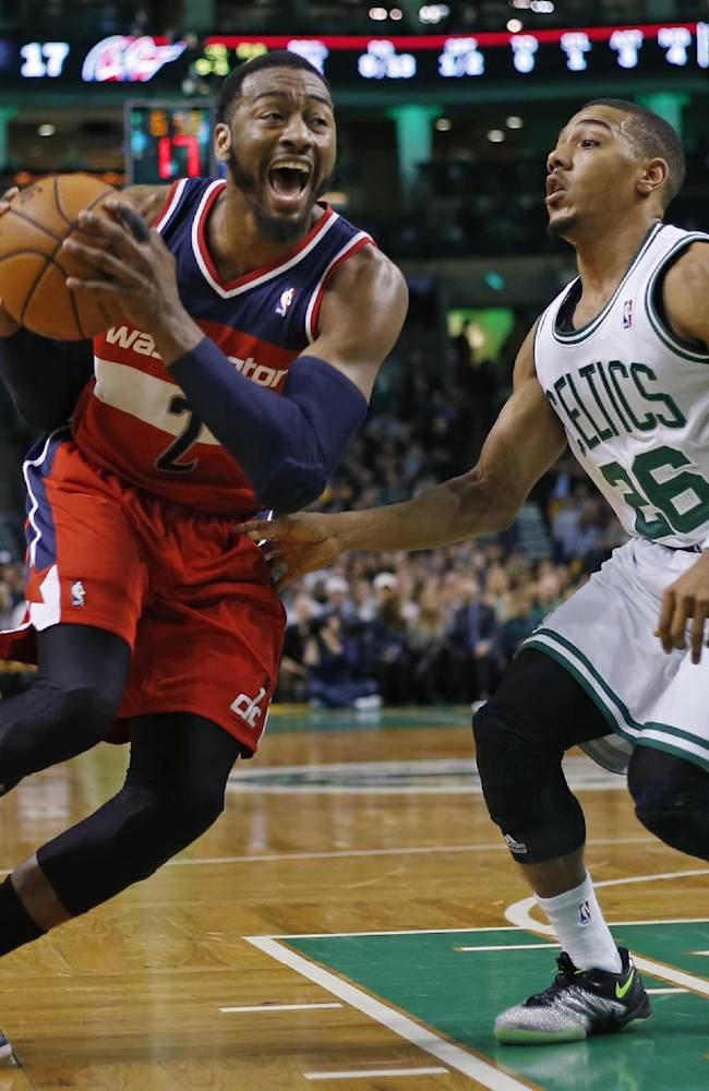 Washington Wizards guard John Wall (2) drives against Boston Celtics guard Phil Pressey (26) during the first quarter of an NBA basketball game in Boston, Wednesday, April 16, 2014