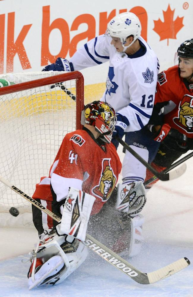 Toronto Maple Leafs' Mason Raymond, center, scores past Ottawa Senators' Craig Anderson, left, as teammate Chris Wideman watches during a preseason NHL hockey game in Ottawa, Ontario on Thursday, Sept. 19, 2013