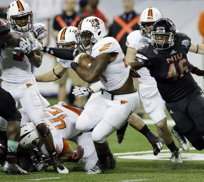 Bowling Green defensive back BooBoo Gates, center, rushes against the Northern Illinois defense during the first half of an NCAA college football game at the Mid-American Conference championship in Detroit, Friday, Dec. 6, 2013