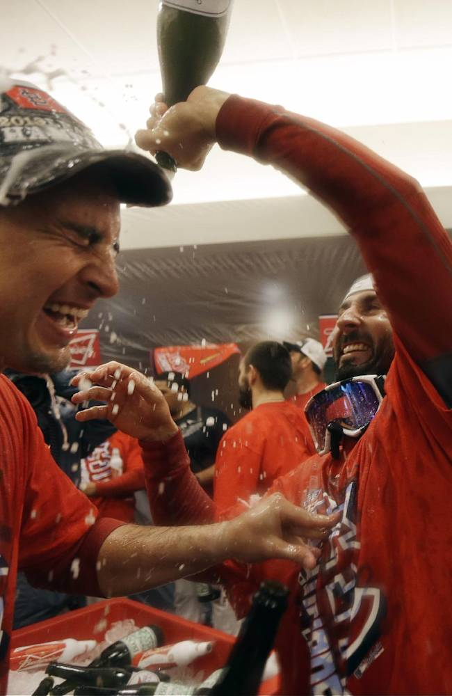 CORRECTS SPELLING OF ALLEN CRAIG FROM ALAN AS ORIGINALLY SENT - St. Louis Cardinals' Allen Craig has Champagne poured on him by teammate Daniel Descalso after Game 6 of the National League baseball championship series against the Los Angeles Dodgers, Friday, Oct. 18, 2013, in St. Louis. The Cardinals won 9-0 to win the series