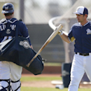 Milwaukee Brewers' Adam Weisenburger, right, hits his bat on Jonathan Lucroy's bag of catching gear after finishing his batting practice during baseball spring training Wednesday, Feb. 26, 2014, in Phoenix The Associated Press