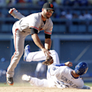 San Francisco Giants second baseman Brandon Hicks, top, leaps over Los Angeles Dodgers' Adrian Gonzalez to turn a double play in the eighth inning of a baseball game on Saturday, April 5, 2014, in Los Angeles The Associated Press