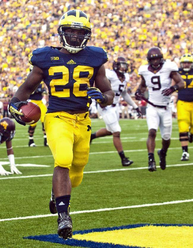 Michigan running back Fitzgerald Toussaint (28) rushes for a 12-yard touchdown in the third quarter of an NCAA college football game against Minnesota, Saturday, Oct. 5, 2013, in Ann Arbor, Mich. Michigan won 42-13