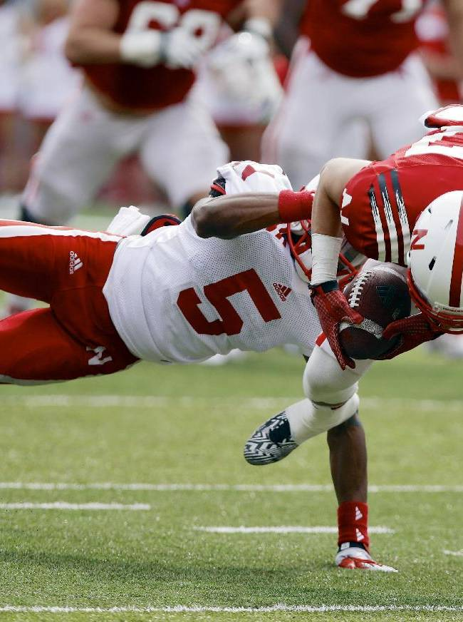 Nebraska wide receiver Brandon Reilly (87) breaks a tackle by cornerback Josh Mitchell (5) during Nebraska's NCAA college football spring game in Lincoln, Neb., Saturday, April 12, 2014