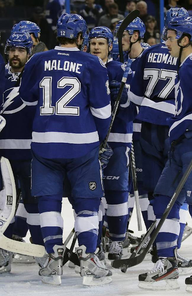 Tampa Bay Lightning goalie Ben Bishop (30) is surrounded by teammates after they defeated the Anaheim Ducks 5-1 during an NHL hockey game on Thursday, Nov. 14, 2013, in Tampa, Fla