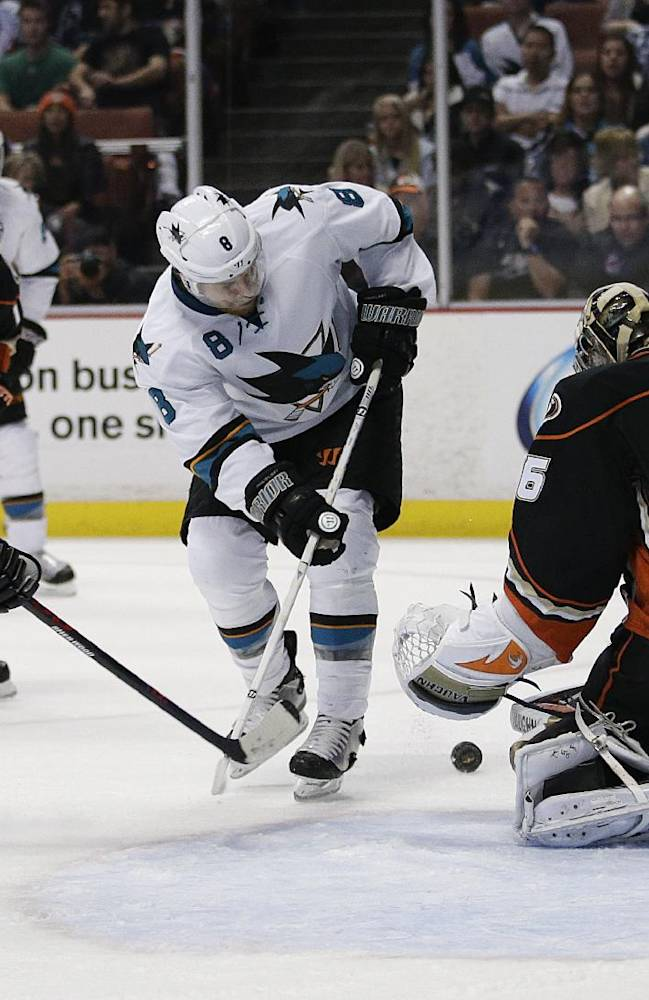 Anaheim Ducks goalie John Gibson, right, stops a shot by San Jose Sharks' Joe Pavelski, center, during the first period of an NHL hockey game Wednesday, April 9, 2014, in Anaheim, Calif